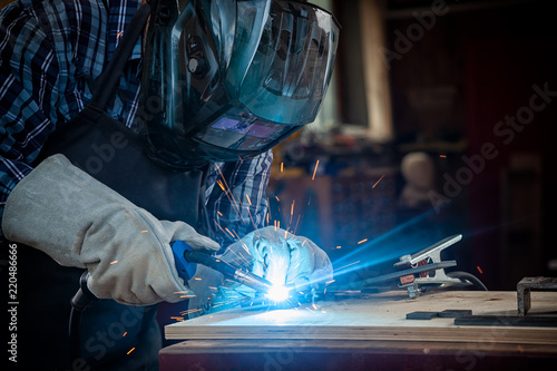 Obraz na plátně  Strong man welder in work clothes hard working and welds with a welding machine metal