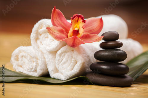 Fototapeta Spa background. White towels on exotic plant, beautiful orchid flower and balancing stones for relax spa massage and body treatment. Asian medicine with aroma and stone therapy for beauty healthy body obraz
