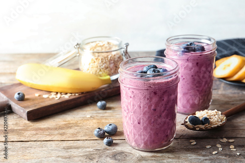 Jars with blueberry smoothies on wooden table