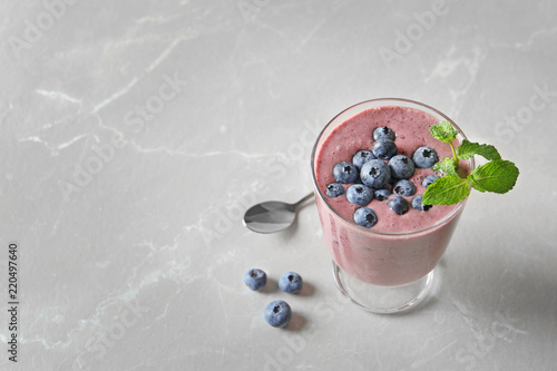 Glass with blueberry smoothie on light background. Space for text