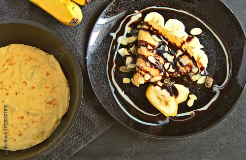 Fotografia  Banana chocolate crepe topping with almond slices on black dish with fresh bananas on black background