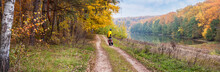 Autumn Landscape, Panorama, Banner - The Road With Cyclist Near Lake In The Sunny Day