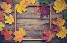Frame Of Autumn Leaves On Wooden Background