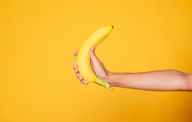 Female hand Holding Banana Fruit, Nutrition concept, human hand holding a ban...