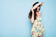 canvas print picture Portrait of cute summer brunette woman in hat and colorful dress, stylish girl have a fun and posing on blue background