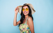 canvas print picture Portrait of cute summer brunette woman in hat, sunglasses and colorful dress, stylish girl have a fun and posing on blue background
