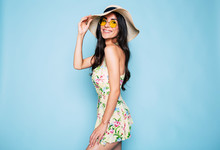 Portrait Of Cute Summer Brunette Woman In Hat, Sunglasses And Colorful Dress, Stylish Girl Have A Fun And Posing On Blue Background