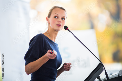 Pretty, young business woman giving a presentation in a conference/meeting setti Canvas Print