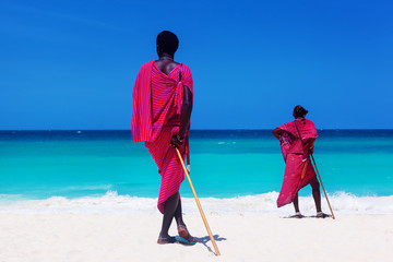 Two maasai warriors looking on ocean.