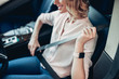 woman fastening safety belt in the car