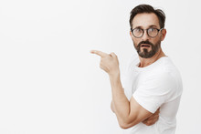 Is It Him. Portrait Of Shocked And Curious Good-looking Mature Guy In Glasses And T-shirt, Standing In Profile And Turning To Camera Asking Question, Pointing Left With Index Finger, Being Interested