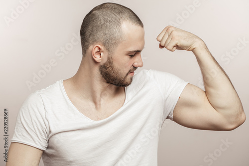Foto close up side view portrait of a muscular young man showing his biceps