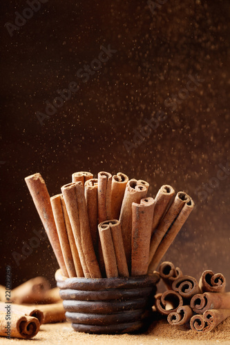 Keuken foto achterwand Kruiderij Cinnamon sticks in bowl and powder on brown background. Aromatic spice.