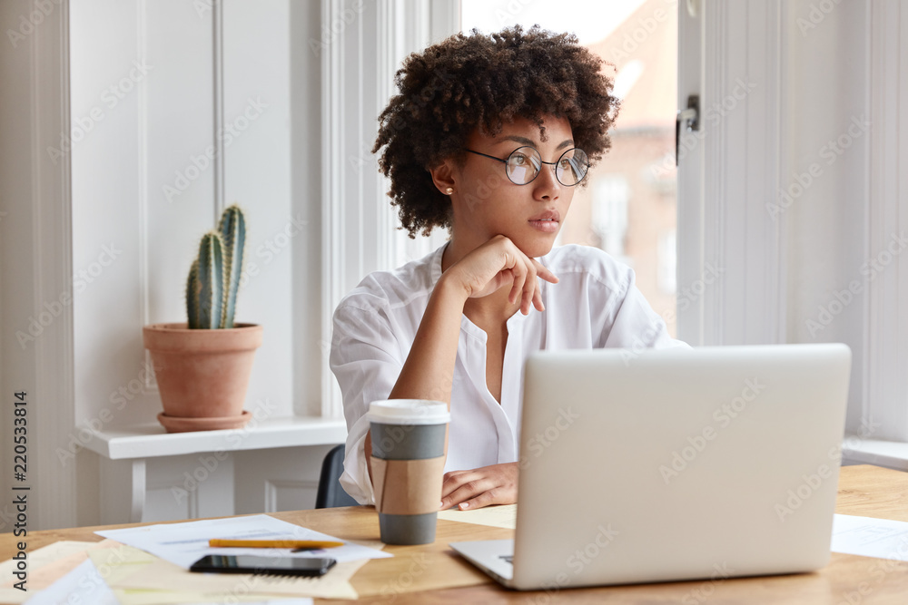 Fototapety, obrazy: Paperwork concept. Experienced thoughtful African American administrative manager works with financial documents and modern electonic gadgets, wears round spectacles, poses against cozy interior