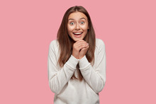 People, Unexpectedness And Emotions Concept. Overjoyed European Woman Clasps Hands From Happiness, Has Broad Smile And Eyes Full Of Delight, Dressed In White Sweatshirt, Stands Indoor Alone.