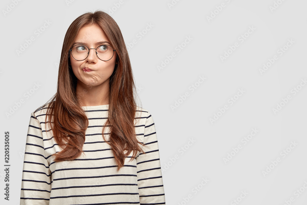 Fototapeta Well, I dont know. Doubrtful thoughtful beautiful woman purses lips, has indecisive expression, being deep in thoughts, isolated over white background with copy space for your promotion or slogan