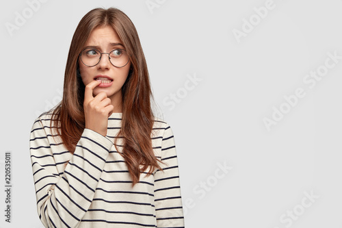 Fotografía  Photo of worried beautiful European woman bites fore finger and looks with hesit