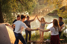 Young Positive People Dancing Around The Campfire.birthday And Day Off Concept. Amazing Scenery On Background Of The Photo