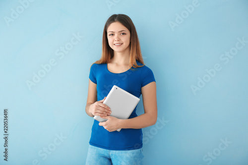 Photo  Teenage girl with tablet computer on color background
