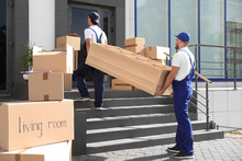 Male Movers Carrying Shelving Unit Into New House