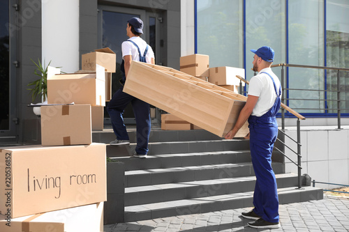 Fotografía  Male movers carrying shelving unit into new house