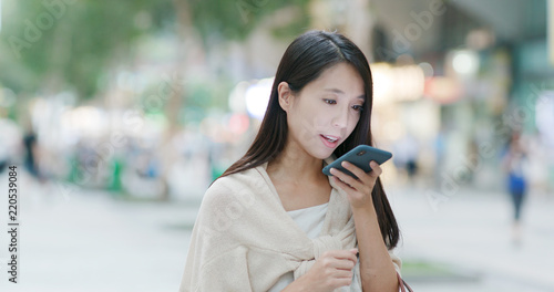 Woman sending audio message on cellphone in city Tapéta, Fotótapéta