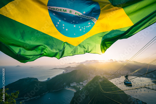 Printed kitchen splashbacks Rio de Janeiro Brazilian flag shines above the golden sunset city skyline at Sugarloaf Pao de Acucar Mountain in Rio de Janeiro.