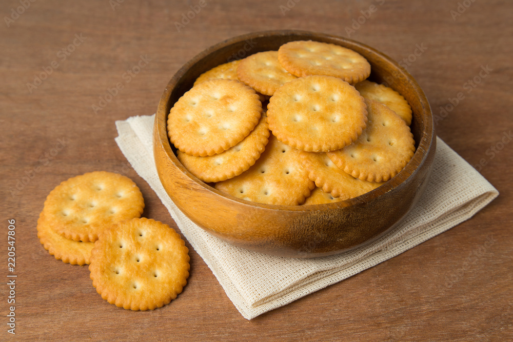 Fototapeta Round salted cracker cookies in wooden bowl putting on linen and wooden background.