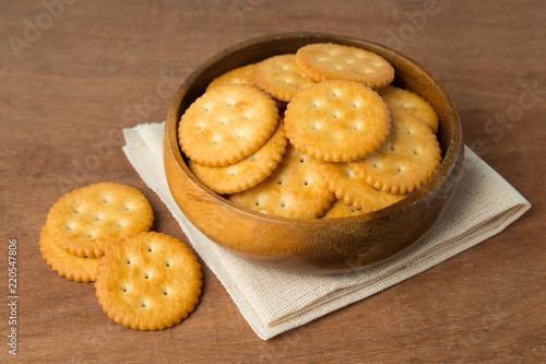 Fényképezés Round salted cracker cookies in wooden bowl putting on linen and wooden background