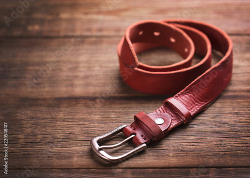 Valokuvatapetti Leather belt on a wooden background. Girdle of red leather.