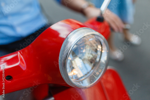 Closeup of round glass headlight red classic scooter. Vintage motorcycle lamp. Beautiful young couple and sitting on classic scooter together. The girl hugs a young man sitting behind on a scooter