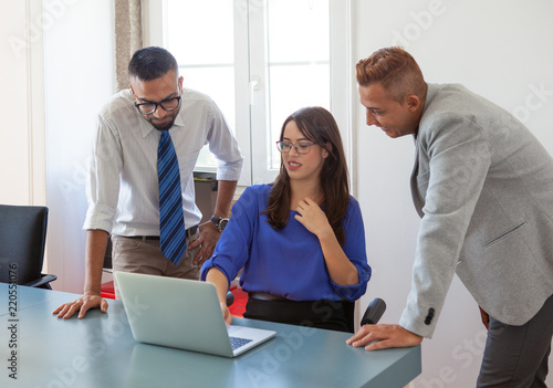 Fototapety, obrazy: Group of experts analyzing marketing report. Three business colleagues studying data on laptop screen. Working together concept