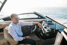 Serious Handsome Business Man Dressed In Classy Style, With Sunglasses Relaxing During Sailing On River, He Sitting Begins The Helm And Driving It On Full Speed.
