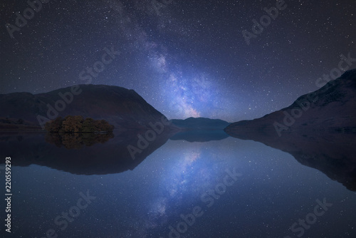 Tuinposter Nachtblauw Vibrant Milky Way composite image over landscape of Crummock Water in Lake District England