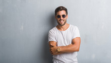 Handsome Young Man Over Grey Grunge Wall Wearing Sunglasses Happy Face Smiling With Crossed Arms Looking At The Camera. Positive Person.