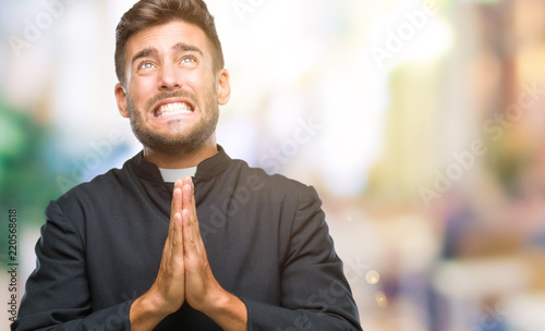 Fotografie, Obraz Young catholic christian priest man over isolated background begging and praying with hands together with hope expression on face very emotional and worried