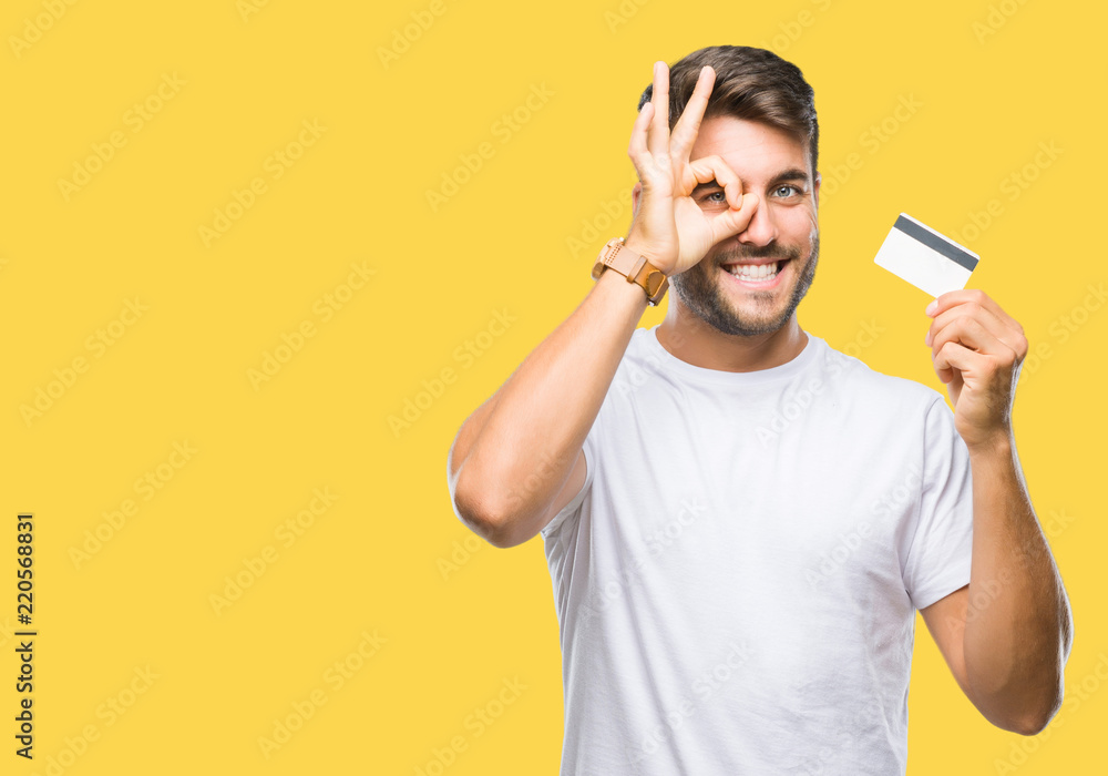 Fototapeta Young handsome man holding credit card over isolated background with happy face smiling doing ok sign with hand on eye looking through fingers