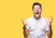 Young handsome man wearing glasses over isolated background crazy and mad shouting and yelling with aggressive expression and arms raised. Frustration concept.