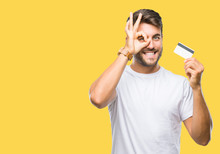 Young Handsome Man Holding Credit Card Over Isolated Background With Happy Face Smiling Doing Ok Sign With Hand On Eye Looking Through Fingers