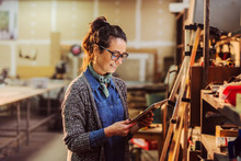 Portrait Of Beautiful Middle Age Industry Female Worker Holding Tablet In Her Hands And Standing In Front Of Shelf With Tools.