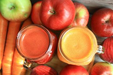 Soki z marchwi, jabłka i buraka, w tle owoce i warzywa