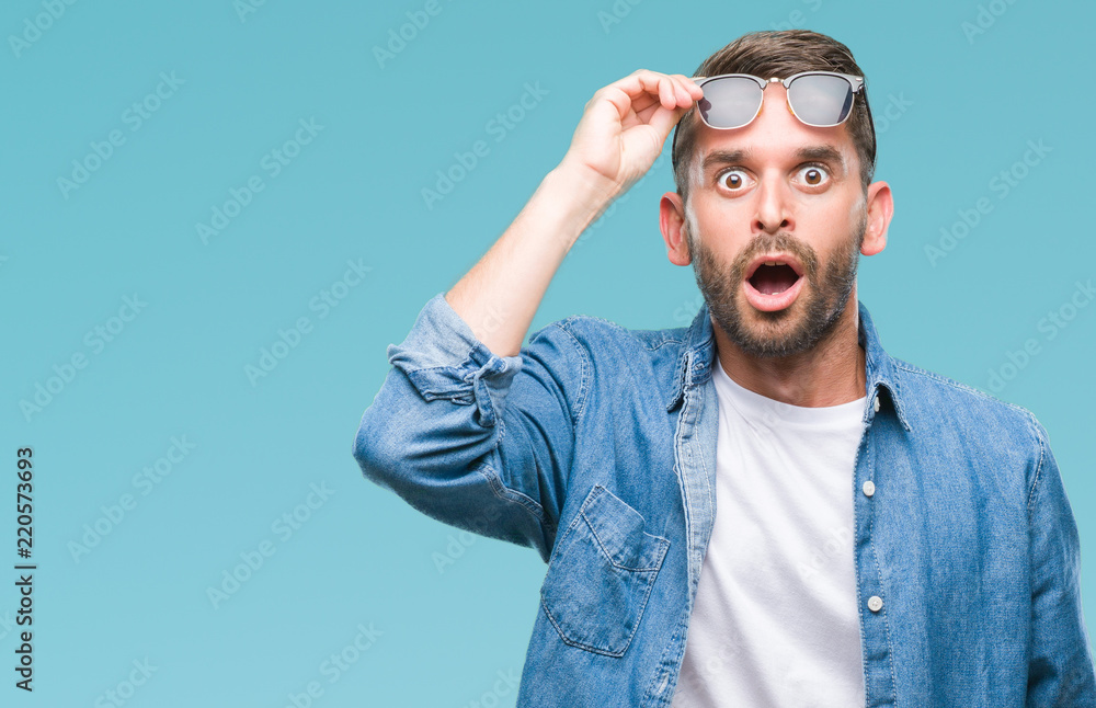 Fototapety, obrazy: Young handsome man wearing sunglasses over isolated background afraid and shocked with surprise expression, fear and excited face.
