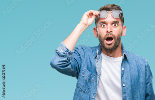 Young handsome man wearing sunglasses over isolated background afraid and shocked with surprise expression, fear and excited face.