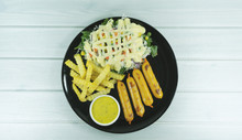 Roasted Sausage Steak And French Fries In Black Dish On White Wood Floor Background Props Decoration With Green Salad, Purple Cauliflower,Top View With Copy Space For Your Text..