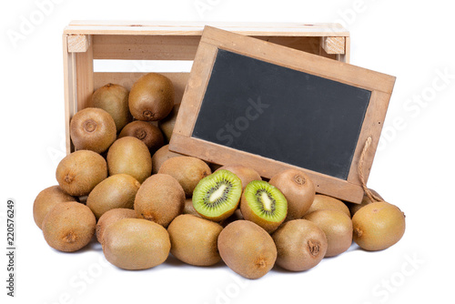 Wooden box filled with many ripe kiwi fruits and two half fruits and a old blank slate blackboard isolated on white background