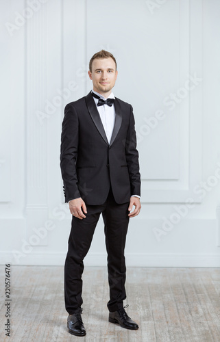 Fotografia Attractive young man in tuxedo smiling and looking at camera