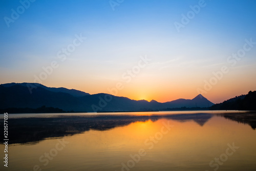 Tuinposter Baksteen Wonderful the lake with sunrise in the evening. attractively nature landscape of golden lake and lagoon. image for background, wallpaper, copy space, decorate and arts.
