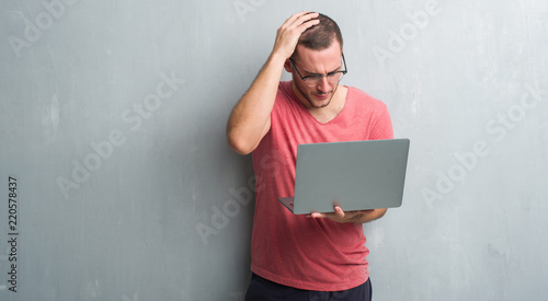 Young caucasian man over grey grunge wall using computer laptop stressed with hand on head, shocked with shame and surprise face, angry and frustrated Fototapeta