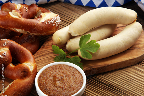 Bavarian veal sausage breakfast with sausages, soft pretzel and mild mustard on wooden board from Germany