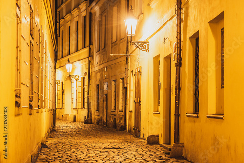 Narrow cobbled street illuminated by street lamps of Old Town, Prague, Czech Republic.